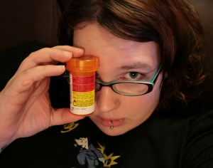 A woman holds up a bottle of pills